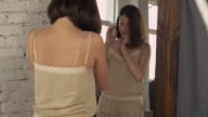 Female looks on reflection in mirror video