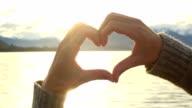 Female makes heart shape finger frame on lake mountain landscape video