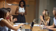 Female manager stands to address female team at a meeting video
