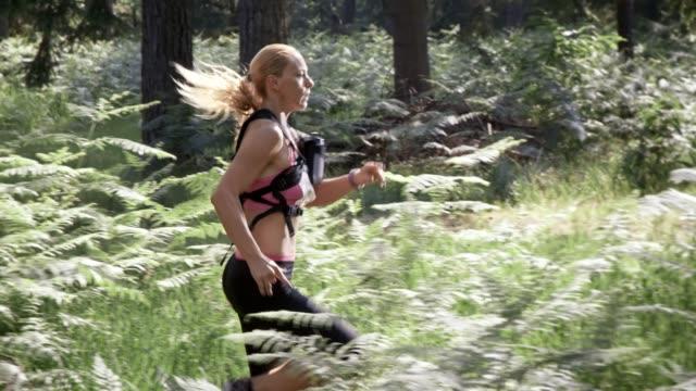 SLO MO DS Female marathon participant running through forest video