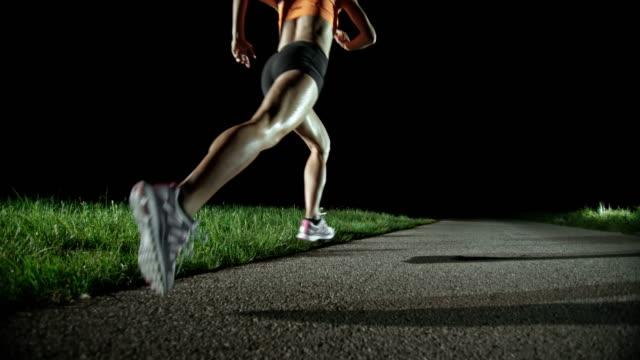 SLO MO PAN Female marathon runner running at night video