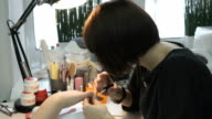 A female master makes manicure of hands girl video