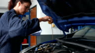 Female mechanic checking oil in the engine video