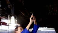 Female mechanic servicing a car video