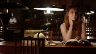 DS Female medical student daydreaming in library at night video