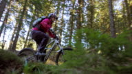 SLO MO Female mountain biker going up the forest trail video