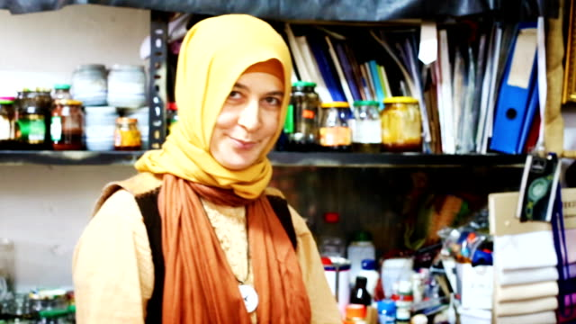 Female Muslim leather worker presenting finished shoe video