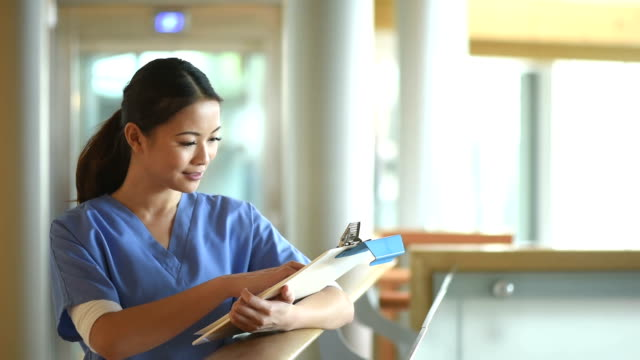 female nurse checking notes in a hospital corridor video