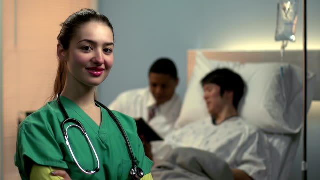 Female nurse standing proudly in front of doctor and patient video