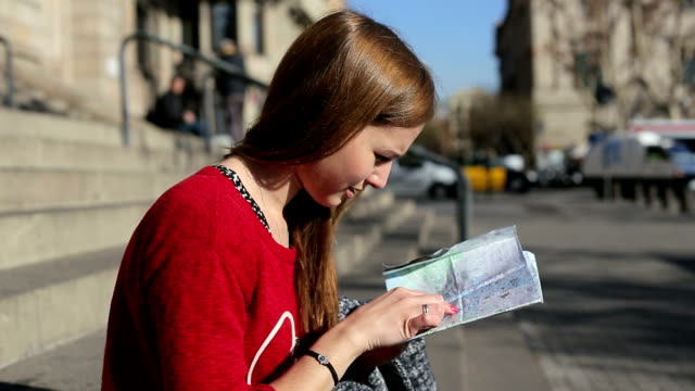 Female on the stairs sees the tourist map looking around traffic behind video