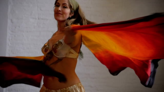 A female performer twirling with colorful fabric wings smiling in slowmo video