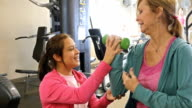 Female personal trainer or physical therapist works with senior client video