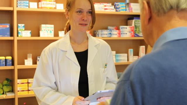 Female Pharmacist Talking To Senior Man In Store video