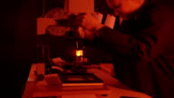 Female photographer working in red darkroom video