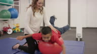 Female physical therapist working with child patient in clinic video
