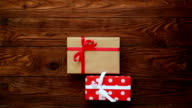 Female placing a group of gift boxes over wooden flat lay video