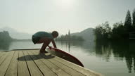 SLOW MOTION: Female placing SUP board into the lake water video