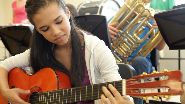 Female Pupil Playing Guitar In High School Orchestra video