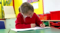 Female Pupil Practising Writing At Desk video