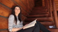 Female reading a book while sitting on the stairs in the cabin. video
