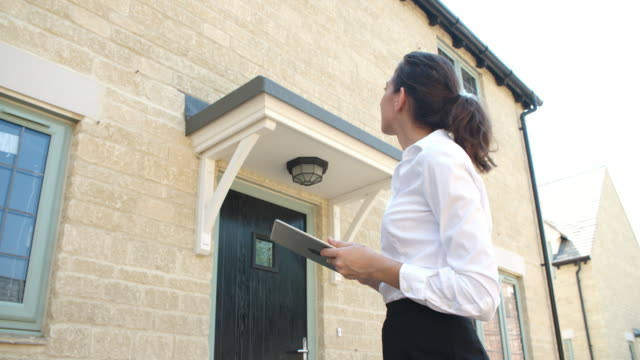 Female real estate agent with digital tablet assessing house video