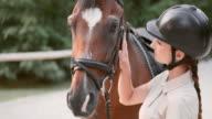 SLO MO Female rider bonding with bay horse video