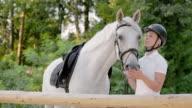 SLO MO Female rider striking her white horse video
