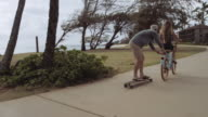 Female riding a bike while towing a man on a longboard video