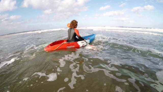 Female Rowing Out to Sea in a Kayak video