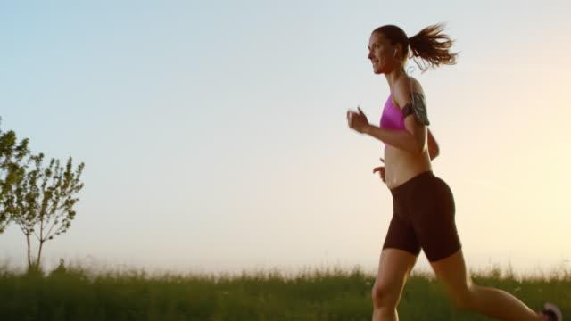 SLO MO TS Female runner at sunset listening to music video