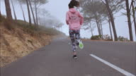 Female runner athlete running on country road video