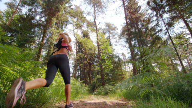 SLO MO DS Female runner running on a forest trail video