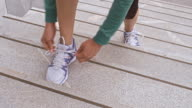 LD Female runner stopping on stairs to tie shoelace video