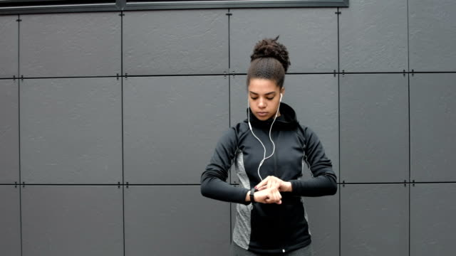 Female runner using activity tracker after workout video