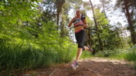 SLO MO CS Female running in marathon across forest clearing video