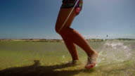 SLOW MOTION CLOSE UP: Female running in shallow water video