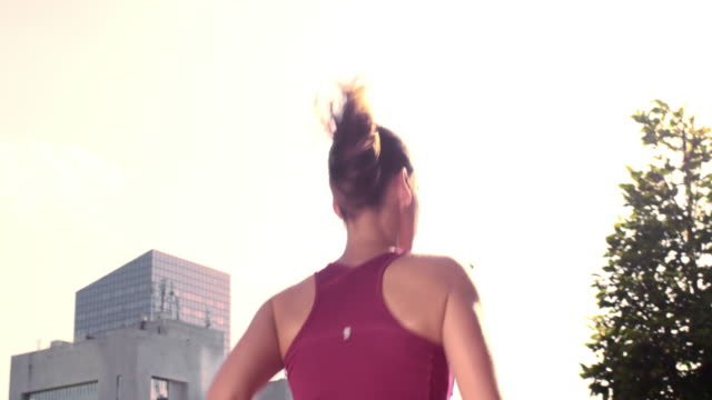 SLO MO TS Female running in the city in sunshine video