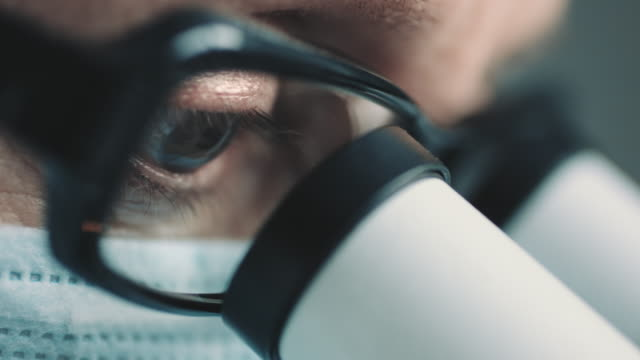 Female scientist looking through microscope video