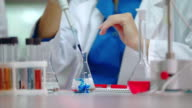 Female scientist pouring reagent in lab flask. Scientist doing chemical reaction video