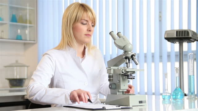 Female scientist using a microscope video