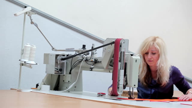 Female seamstress stitches the orange cloth video