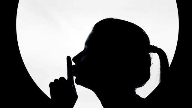Female silhouette making finger on lips gesture, top secret information, gossip video