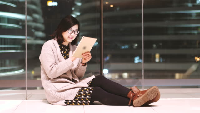 Female Sitting on the Ground and Using Tablet in City at Night video