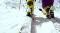 SLO MO Female skier stepping into the binding and starting video