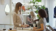 Female small business owner processing payment for female customer video