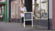 Female small business owner standing outside of her bakery video
