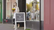 Female small business owner standing outside of her flower shop video
