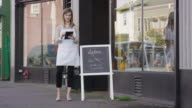 Female small business owner standing outside of her hair salon video