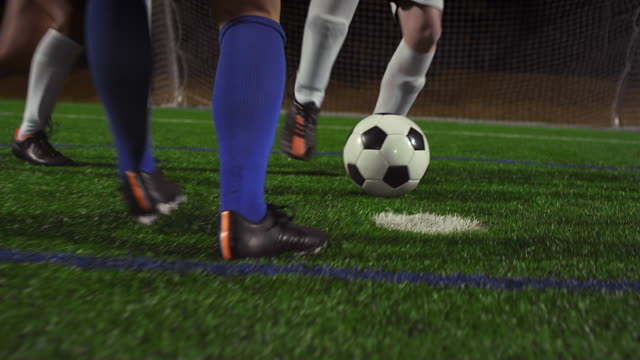 A female soccer player dribbles down the field during a game at night video