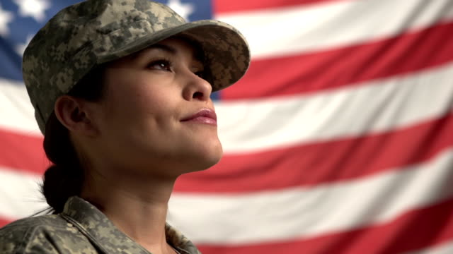 Female Soldier in front of flag, looking up video